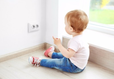 baby on the floor playing with an electrical outlet
