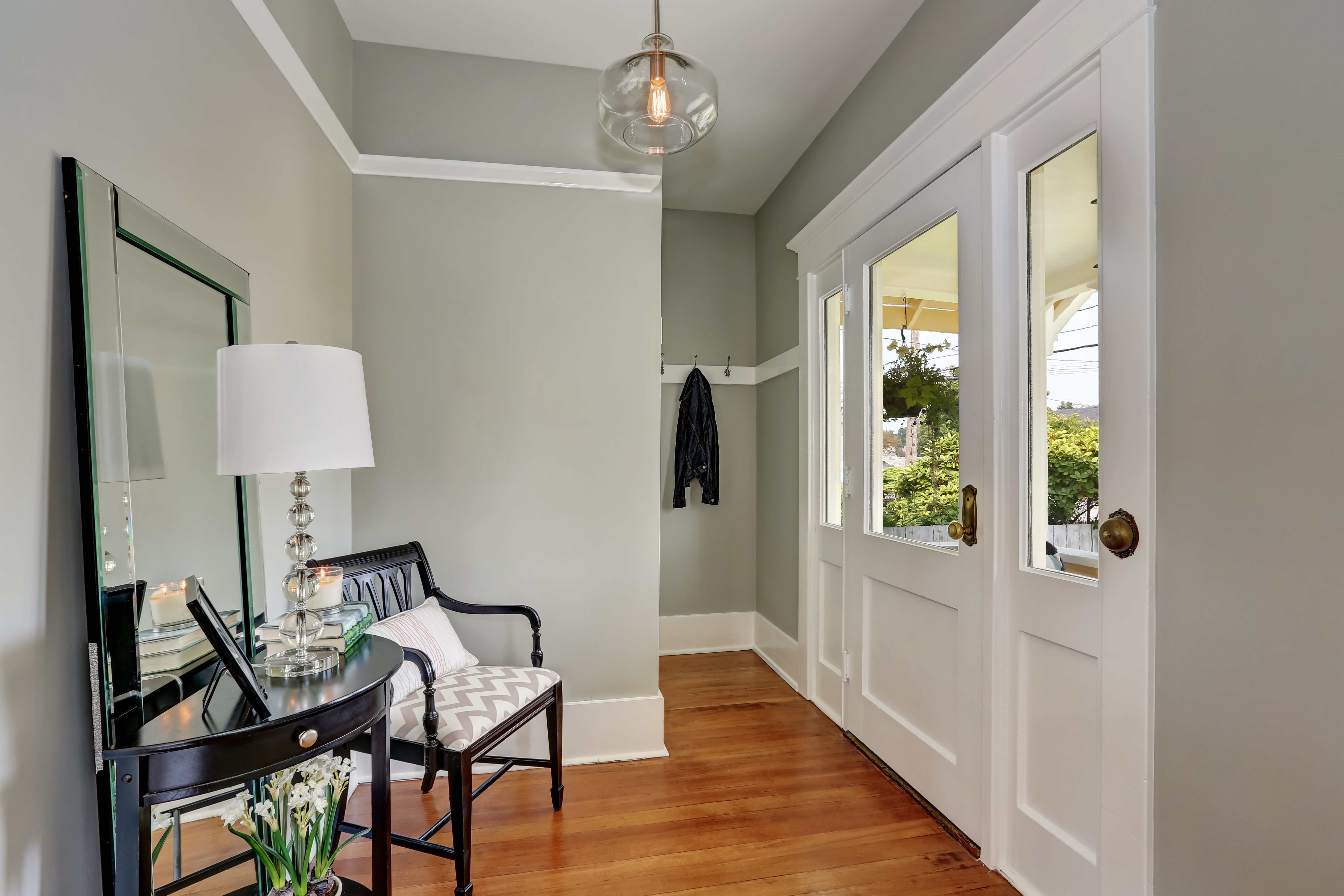 modern home entryway with light grey walls, a decorative mirror, table, and chair
