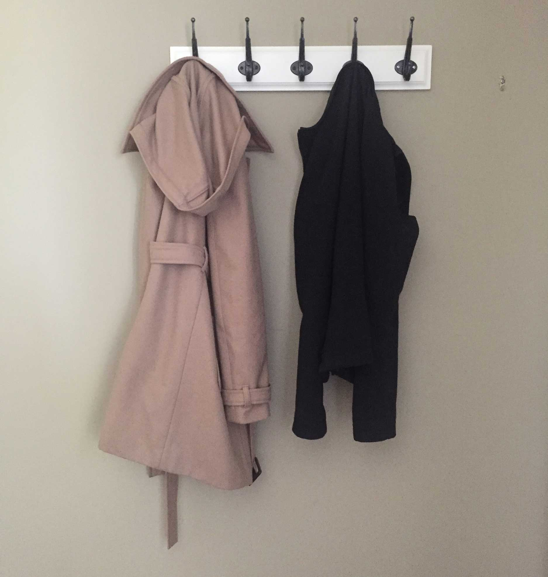 beige wall in home with small hole in drywall hidden by a pea coat hanging on a horizontal coat rack