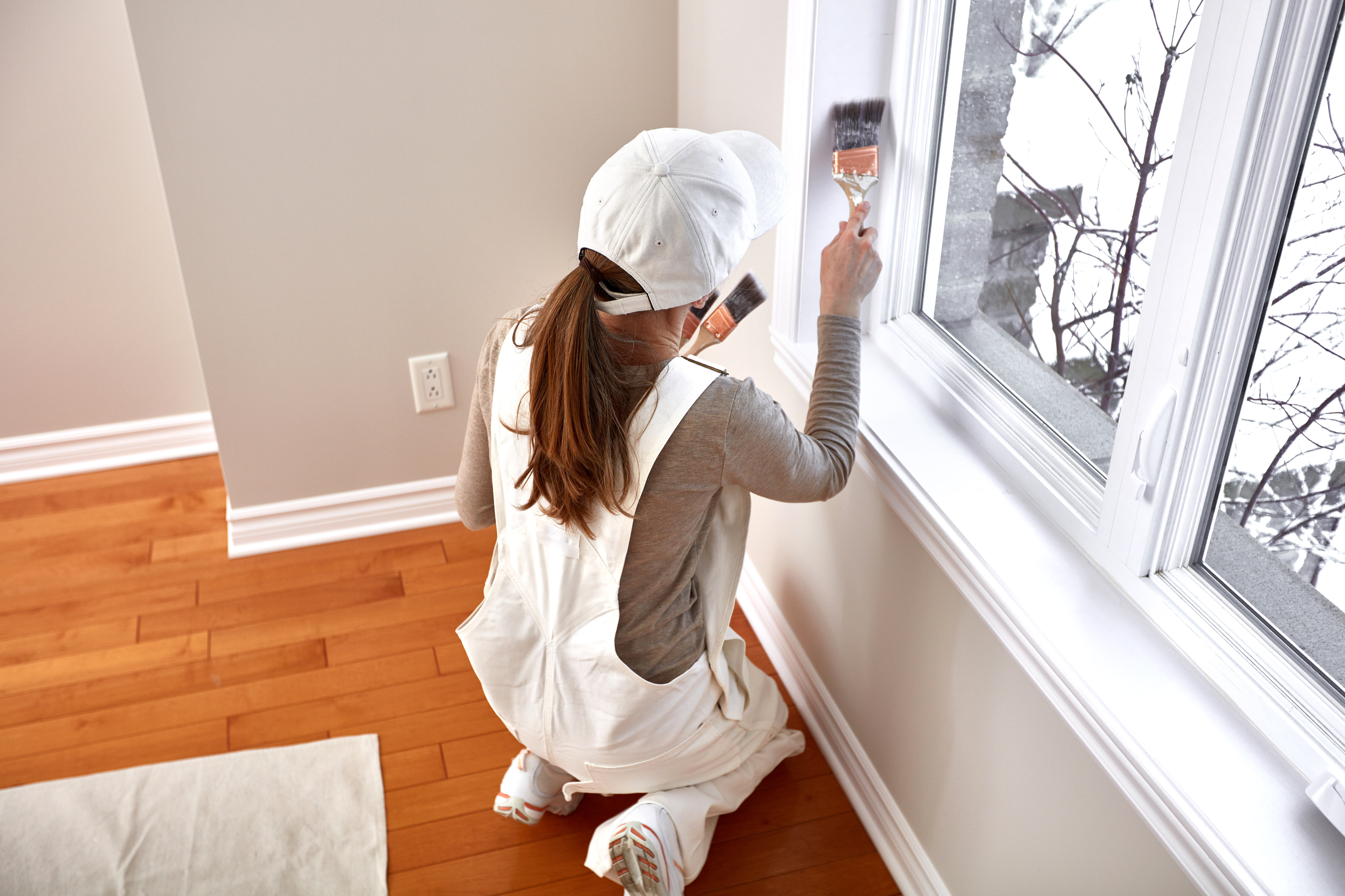 woman painting home interior trim around window frame