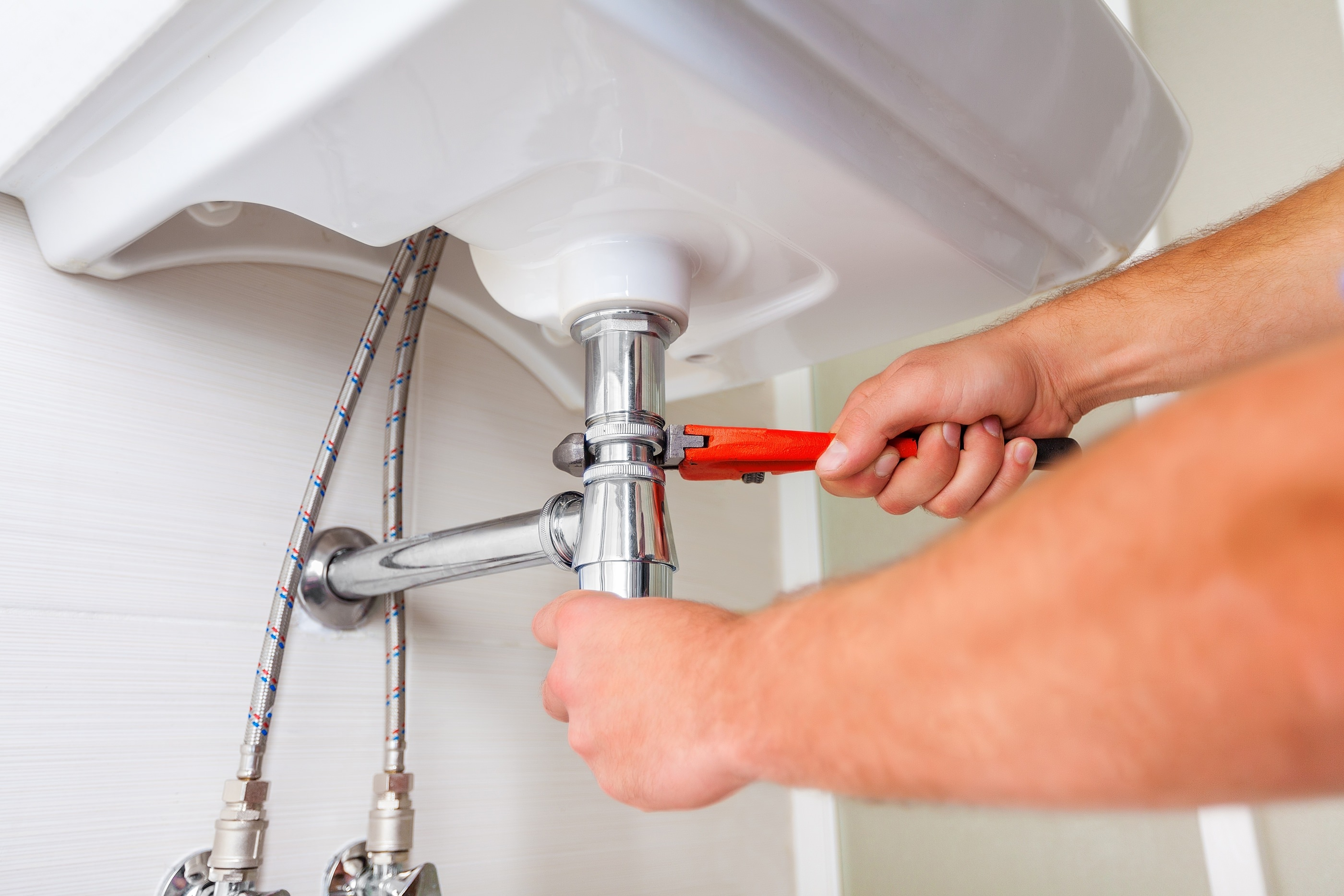 man fixing pipes under a white sink with a red wrench