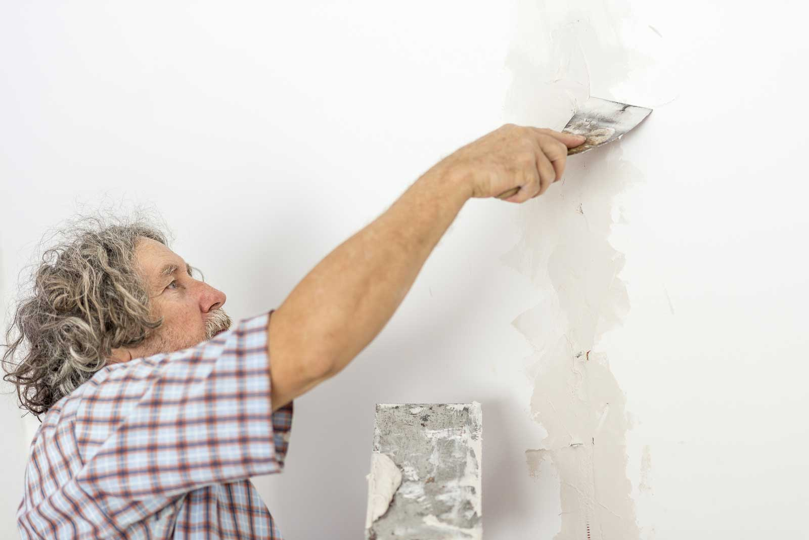 Man repairing large vertical crack in sheetrock with drywall spatula