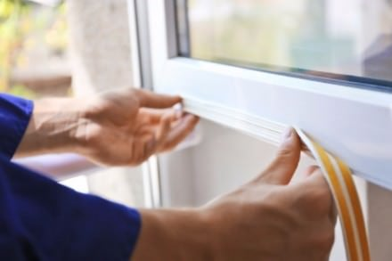 man sealing home windows with foam tape